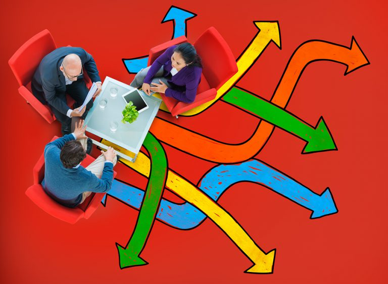 Three people sitting at a desk surounded by arrows indicating the many directions a project can take